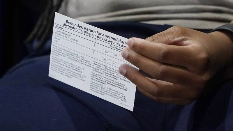 Jniya Tallie fiddles with her vaccination card after receiving her second dose of the Pfizer...