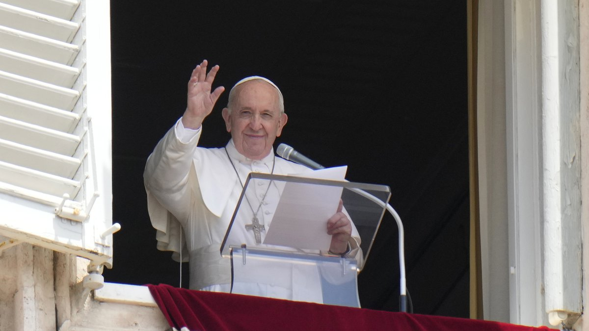 Pope Francis waves to the crowd as he arrives to recite the Angelus noon prayer from the window...