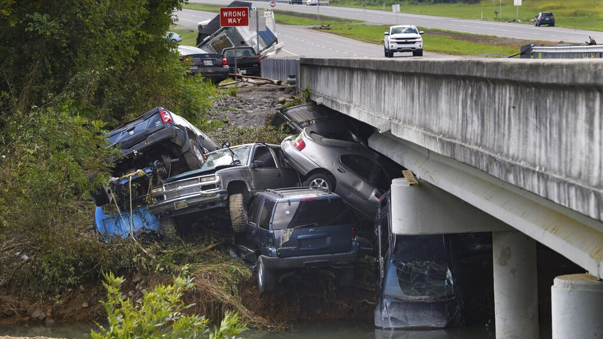 Cars are stacked on top of each other on the banks of Blue Creek being swept up in flood water,...