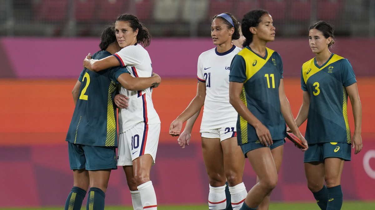 United States' Carli Lloyd, 2nd left, and Australia's Sam Kerr embrace each other at the end of...