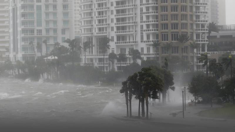 Waves crash over a seawall at the mouth of the Miami River from Biscayne Bay, Fla., as...