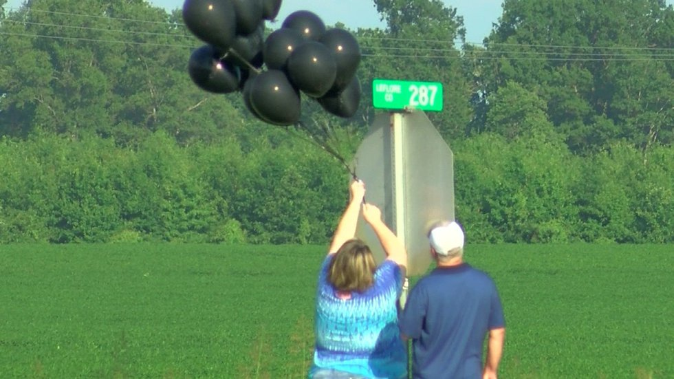 Brenda Cockrell placed black balloons by the road that leads to a portion of the wreckage....