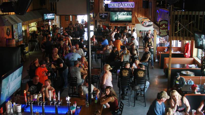 FILE - In this Aug. 7, 2020, file photo, people fill a bar during the Sturgis Motorcycle Rally...
