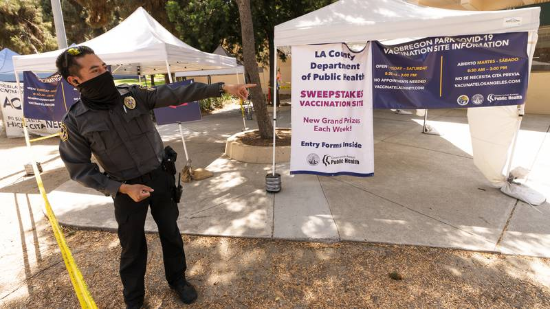 A private security guard gives directions to people looking to get vaccinated, as banners...