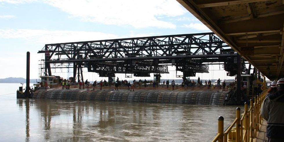 An image of a barge sinking concrete mats in the Mississippi River.