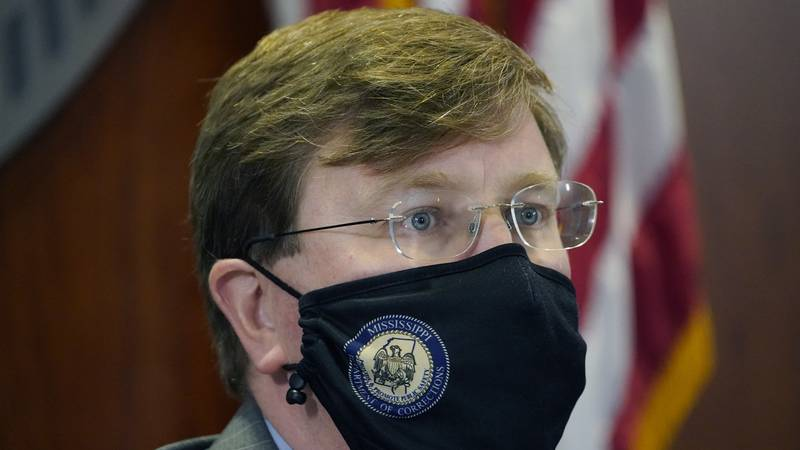 Mississippi Gov. Tate Reeves wears a face mask as he listens to Mississippi State Health...