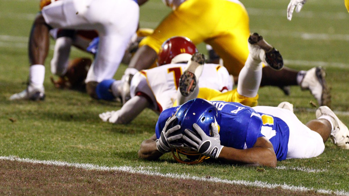 Oxford running back Kenzie Phillips reacts after fumbling the ball near the goal line, while...