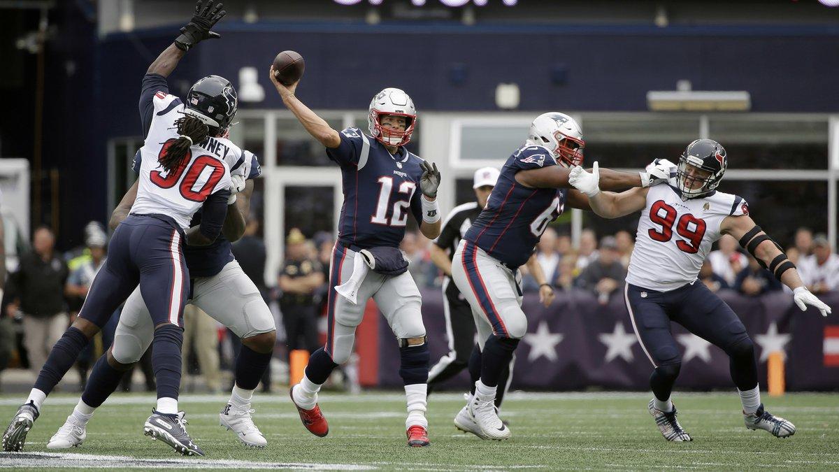 New England Patriots quarterback Tom Brady (12) passes under pressure from Houston Texans...