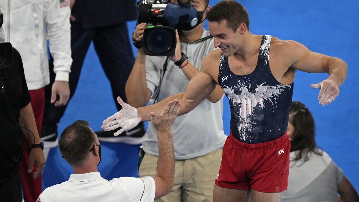 Samuel Mikulak, of the United States, gives a high five to a member of his team after...