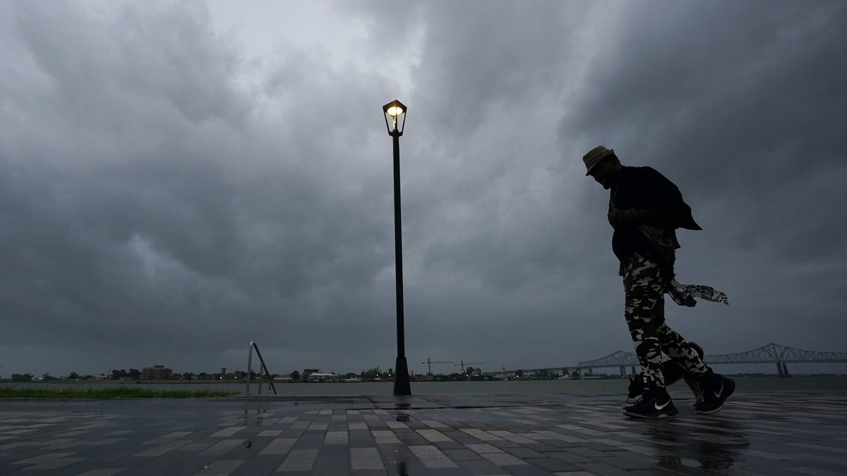 A man walks along the Mississippi River near the French Quarter as the sun rises and the early...