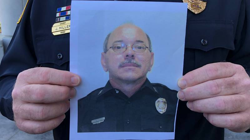 Chief Miller holds a photo of Officer Robert McKeithen during a press conference Monday...