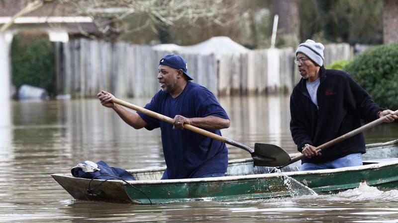 Jackson, Miss., homeowners use shovels to work their way through Pearl River floodwater in this...