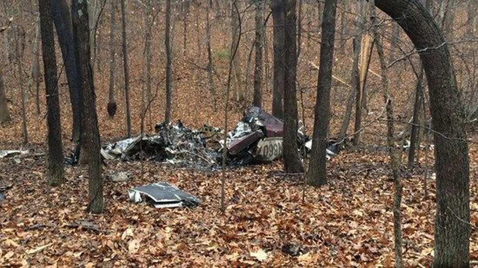The plane crashed two miles from the airport in a wooded area.