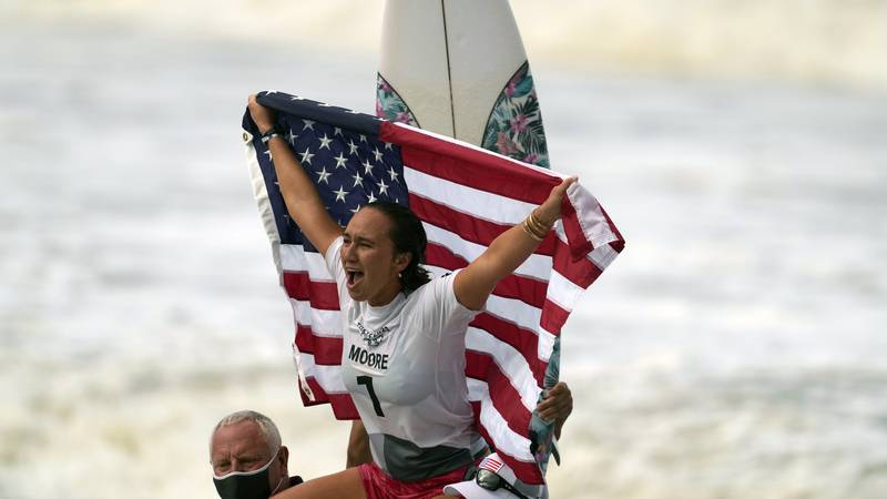 Carissa Moore, of the United States, celebrates winning the gold medal of the women's surfing...